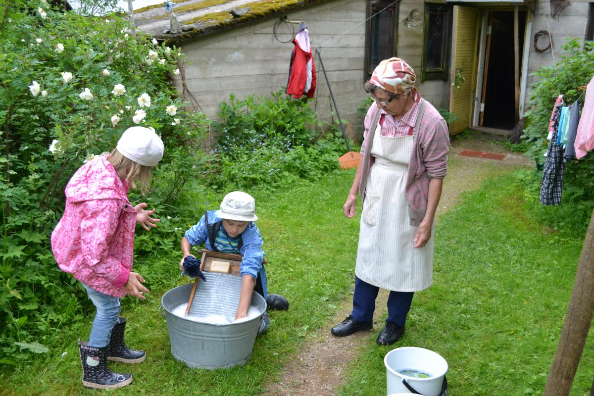 Lasten perinnepäivä koostuu työkokeiluista ja leikeistä. Kuvassa Eila Lempinen näyttää pyykinpesua pyykkilaudalla.