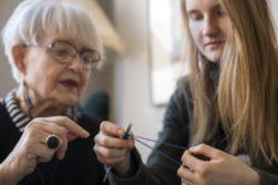 Ikäihminen opettaa nuorta neulomaan