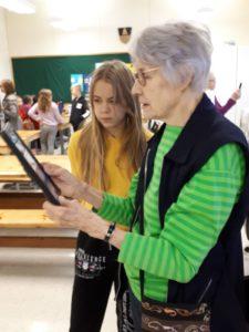 Nuori opettaa tabletin käyttöä ikäihmiselle