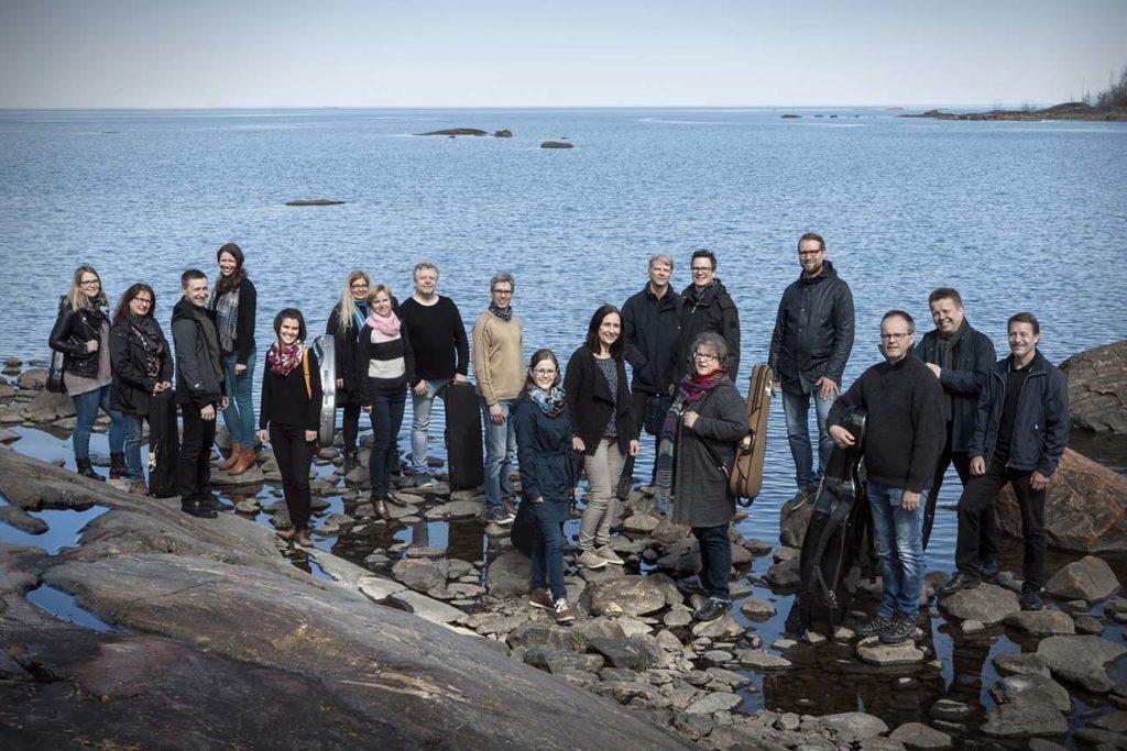Keski-Pohjanmaan kamariorkesterin jäseniä meren rannalla.