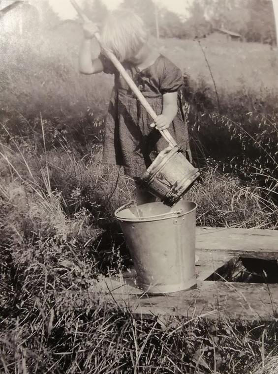 Vanha valokuva, jossa on tyttö hakemassa vettä.
