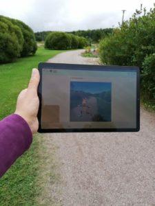 Tabletti jossa näkyy tietoa paikasta. Taustalla puistikko.