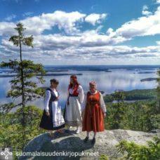 Kansallispukuisia naisia Kolin maisemissa.