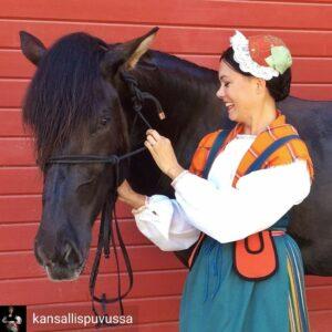 Kansallispukuinen nainen ja hevonen.
