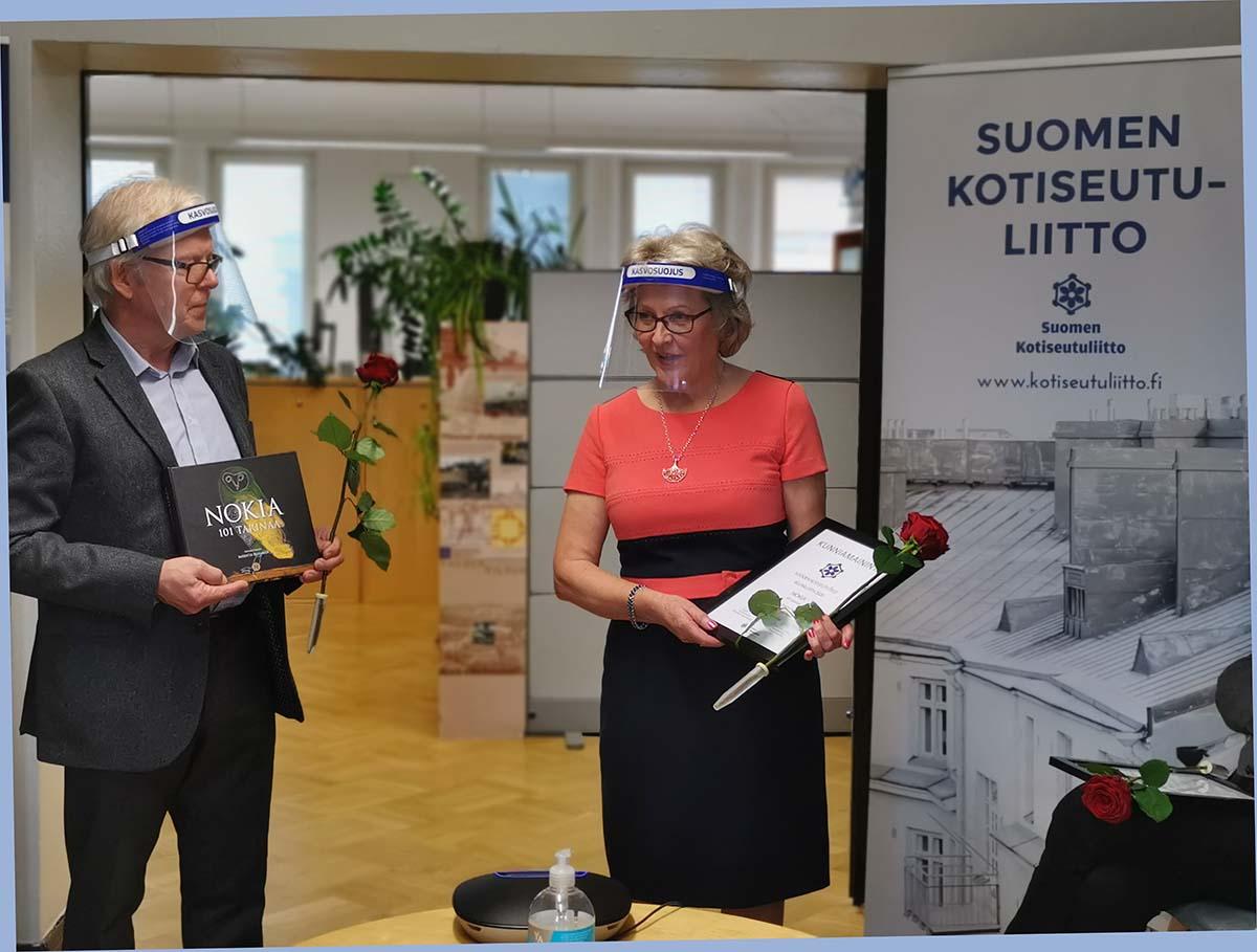 Veijo Hynninen ja Maritta Pahlman tilaisuudessa visiirit päässä ja kukat kädessä.