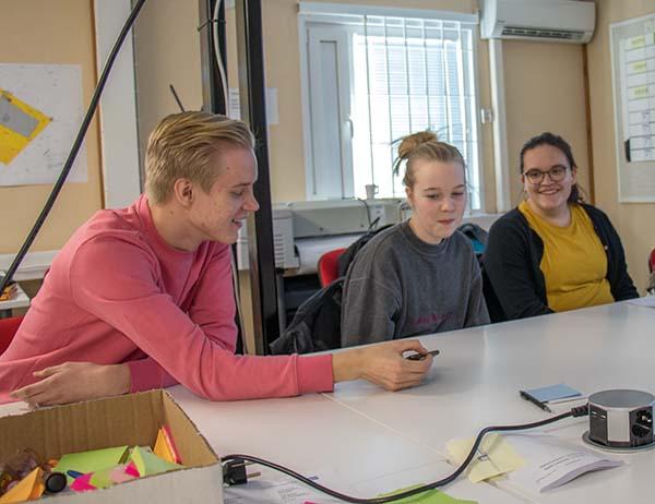 Kolme nuorta suunnittelupöydän äärellä.