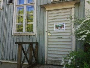 """Kuva puutalosta, jonka ovessa on juliste: """"Kylätila käpyläläisille""""."""