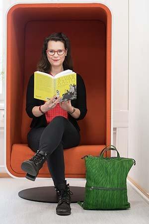 Laura Lehtinen kädessään Alvar Aaltoa käsittelevä kirja.