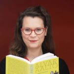 Laura Lehtinen, lukee Alvar aallosta kertovaa kirjaa.