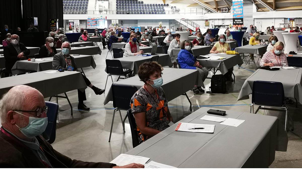 Kotiseutuliiton vuosikokous, ihmisiä pöytien ääressä.